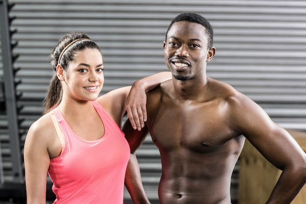 Fit couple with hands on hips at crossfit gym