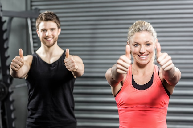 Fit couple with thumbs up at crossfit gym