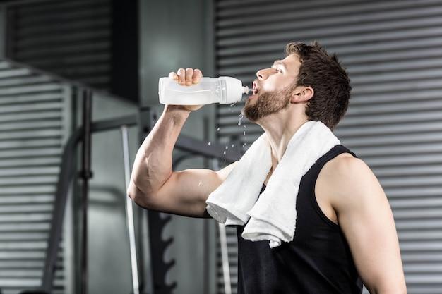 Fit мужчина питьевой воды в тренажерном зале crossfit