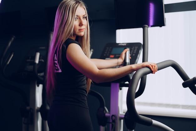 Фигуристая молодая блондинка тренируется в кардиозоне в тренажерном зале