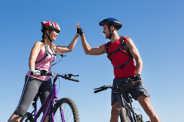 Fit cyclist couple standing at the summit high fiving