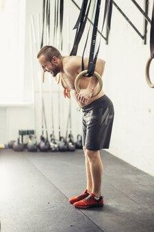 フィットディップリング男は、ジムの浸漬運動でトレーニングする準備します。