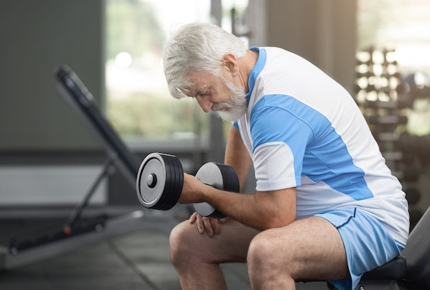Fit elderly man working out with dumbbells in gym.