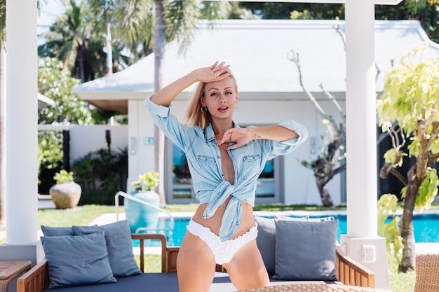 블루 데님 셔츠와 흰색 비키니 팬티에 짧은 금발 머리를 가진 유럽의 아름다운 여인을 맞추십시오.