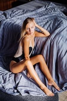 침실에 베이지 색 바디 수트에 일출 빛에 침실에 유럽 여성을 적합