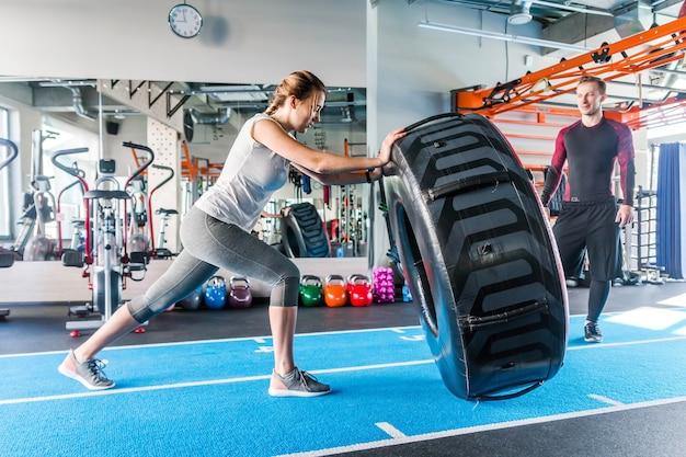 Подходит спортсменка, тренирующаяся с огромной покрышкой, переворачивая и переворачиваясь в тренажерном зале. женщина crossfit работая с большой покрышкой.