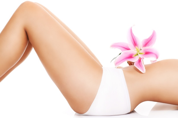 Fit female body and flower on white background