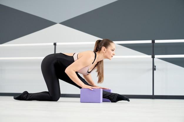 Fit female dancer stretching legs using small blocks