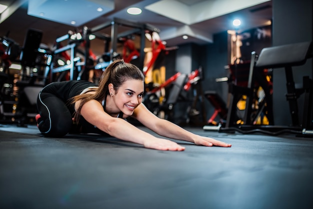 Fit female doing stretching workout on the gym floor.