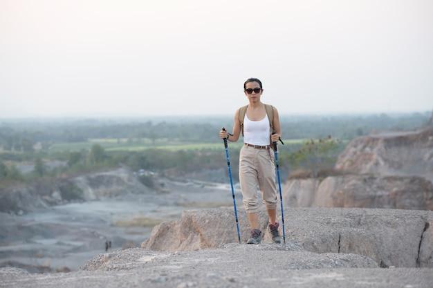 Подходящая туристка с рюкзаком и шестами стоит на скалистом горном хребте, глядя на долины и вершины.