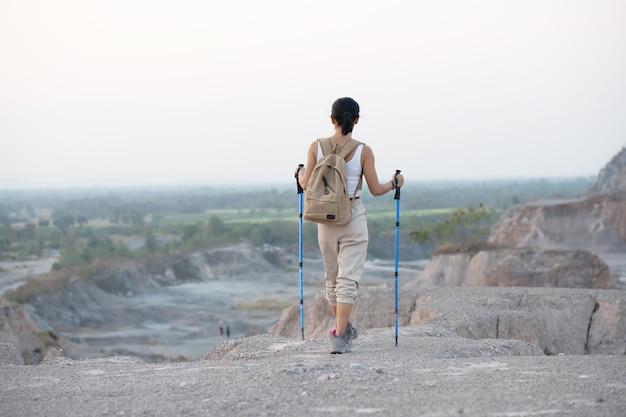 배낭과 기둥이 계곡과 봉우리를 바라 보는 바위 산 능선에 서있는 여성 등산객에게 적합합니다.