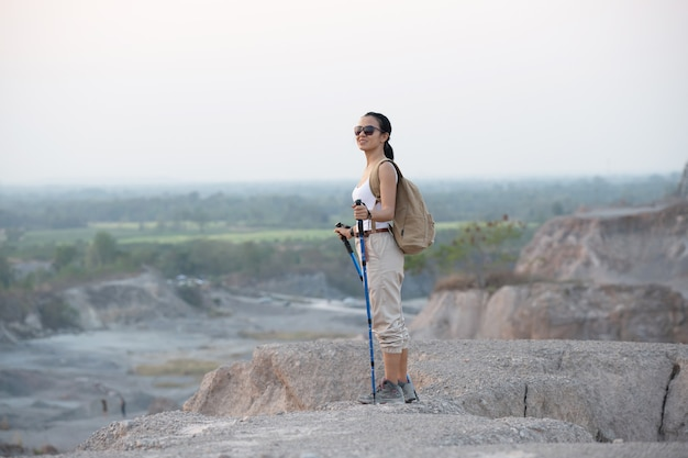 Fit female hiker with backpack and poles standing on rocky mountain ridge looking out valleys and peak.