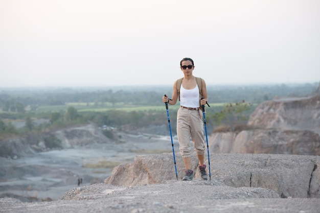 Fit female hiker with backpack and poles standing on rocky mountain ridge looking out valleys and peaks.