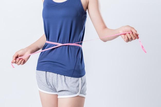 측정 테이프를 가진 그녀의 허리 둘레를 측정 맞는 피트 니스 소녀
