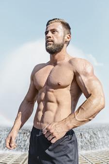 Uomo adatto di forma fisica che posa alla città