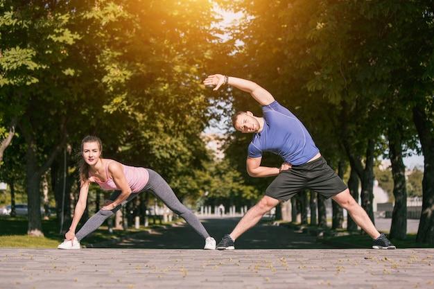 La donna adatta e l'uomo di forma fisica che fanno l'allungamento si esercitano all'aperto al parco