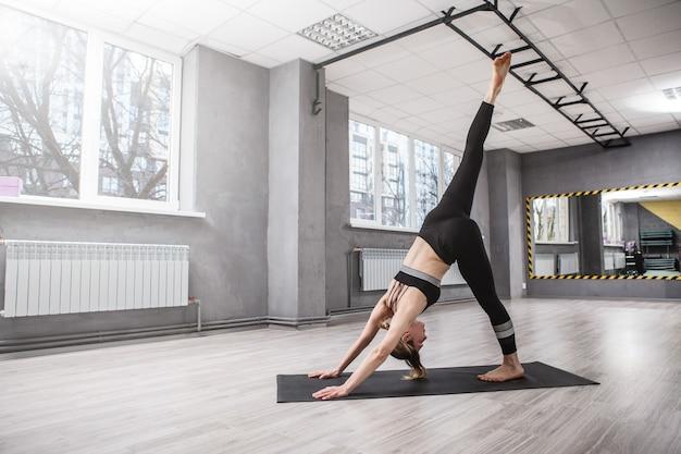 スポーツスタジオでヨガを練習する柔軟な女性にフィット