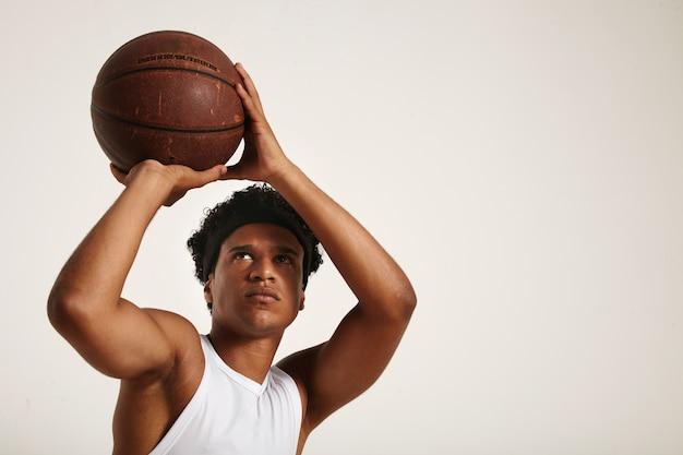 흰색 민소매 셔츠에 짧은 아프리카와 함께 집중된 아프리카 계 미국인 선수가 오래된 가죽 농구를 던질 준비를합니다.