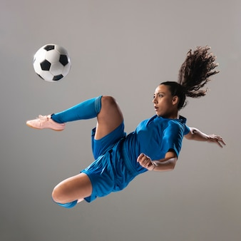 Fit football in sportswear doing tricks
