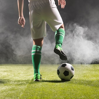 Fit footballer in sportswear with ball Premium Photo