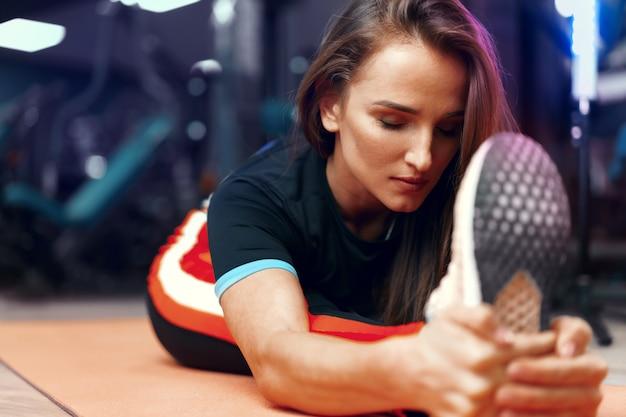 足のストレッチ運動をしているフィットの女の子