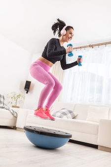 ピンクのヨガパンツと黒のシャツを着た女の子はヘッドフォンを着用し、自宅で青いダンベルとバランスボールを使ってトレーニングを行います。