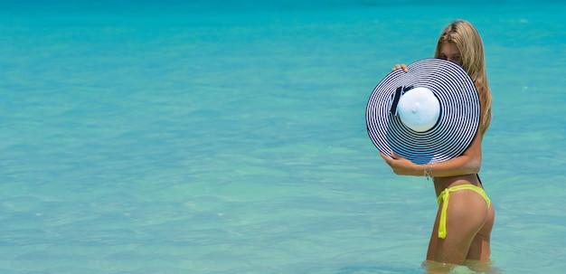 열 대 해변에 맞는 소녀. 여행 휴가에 섹시 비키니 여자 premium photo