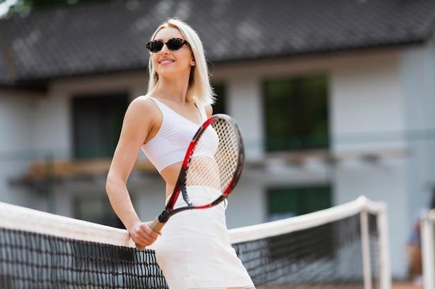 Подходящая девушка позирует на теннисной сетке