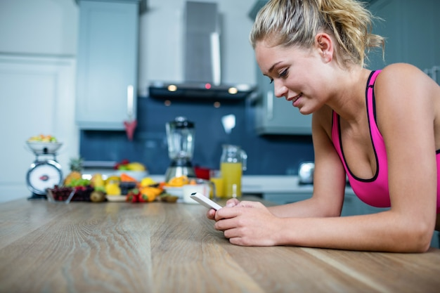 Fit girl sending text messages in the kitchen