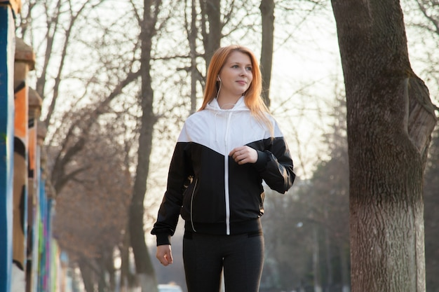 Fit girl sports walking in the morning street