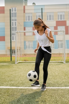 Fit girl in sportswear standing on sports field while kicking soccer ball during training in urban environment