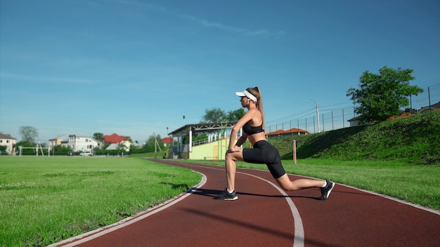 Fit girl stretching legs before training at stadium in summer sunny day. side view of gorgeous young woman girl wearing sportswear and sunglasses practicing lunges outdoors. workout concept.