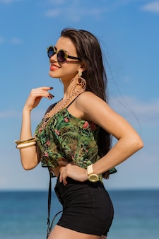 Fit girl in trendy cool sunglasses with tan body posing on the tropical beach wearing bright colored top, hight shorts and stylish swag accessories .