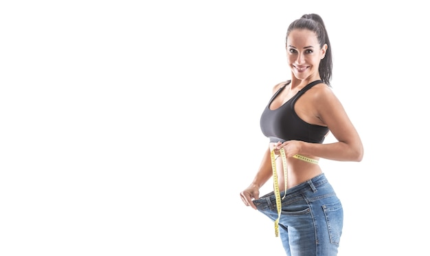 Fit good-looking woman shows great weight loss by loose jeans wearing sports bra on an isolated white background.