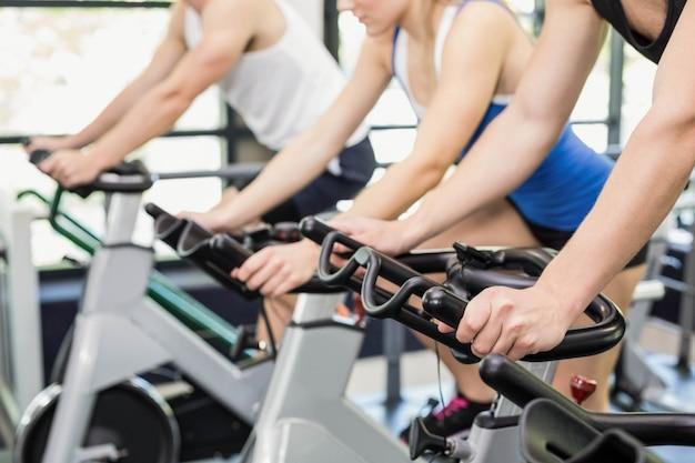 체육관에서 운동 자전거를 함께 사용하는 사람들의 그룹에 맞게