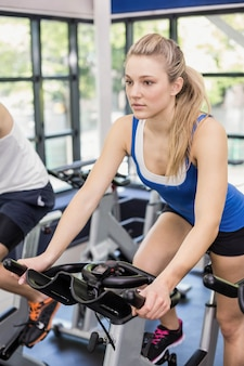 Fit group of people using exercise bike together in gym