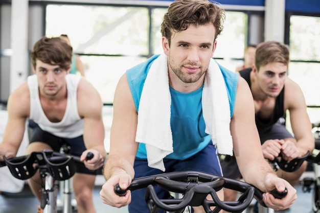 Fit group of people using exercise bike together at gym