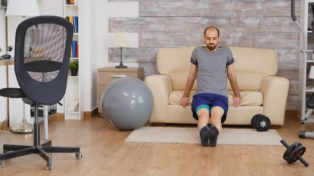 Fit guy training tricipiti sul divano di casa indossando abbigliamento sportivo.