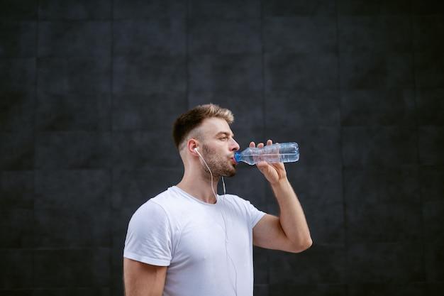 ハンサムな白人のひげを生やした金髪スポーツマン飲料水と暗い壁の前に立っている間耳にイヤホンを合わせてください。