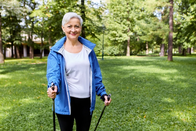 Fit happy gray haired mature female in sportswear enjoying health-promoting physical activity using walking poles having excited joyful facial expression, breathing fresh air in wild nature, smiling