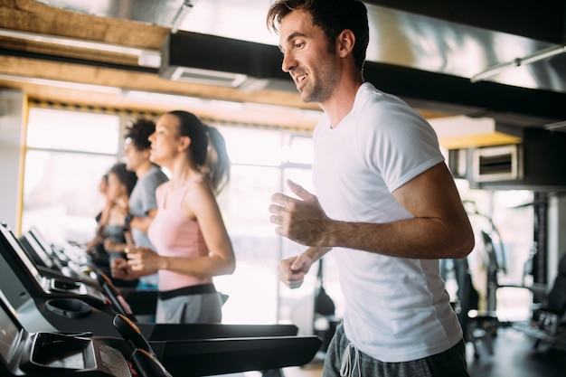 Fit happy people running in machine treadmill at fitness gym