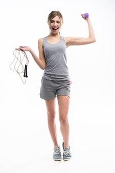白の上にカメラを見ている縄跳びとダンベルを持って幸せな女性に合います。