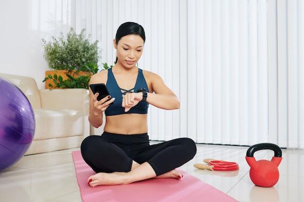 Подходит счастливая молодая женщина, проверяющая приложения на смарт-часах и смартфоне, когда готовится к тренировке дома