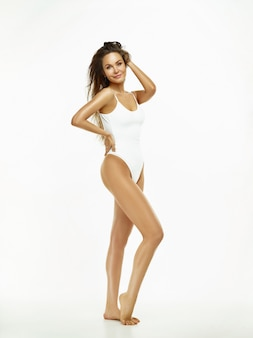 Fit, healthy and sporty girl in swimsuit at studio. sport, fitness, diet and healthcare concept.