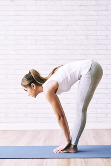 Fit healthy woman doing bend forward at the yoga class