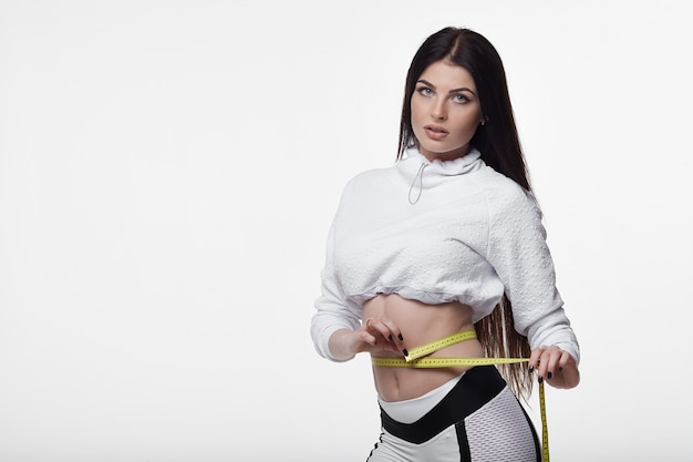 Fit and healthy young lady measuring her waist with a tape measure in centimeters and millimeters. isolated image on white.