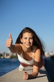 Подходящая радостная женщина в розовых леггинсах делает упражнения на планке, работая над мышцами живота и трицепсами, показывая большой палец вверх, на открытом воздухе. спортивная женская модель делает тренировку crossfit на набережной.