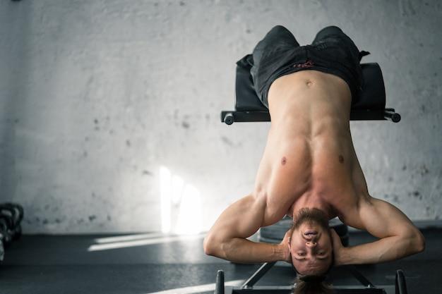 Fit худой молодой человек упражняется в тренажерном зале