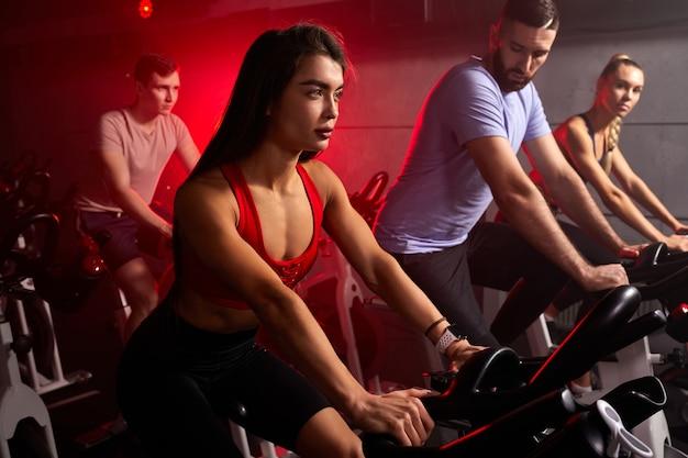 男性と女性をジムにフィットさせ、完璧な形の筋肉質の人々を自転車でトレーニングし、フィットネスジムで有酸素運動を行い、マシンで減量します