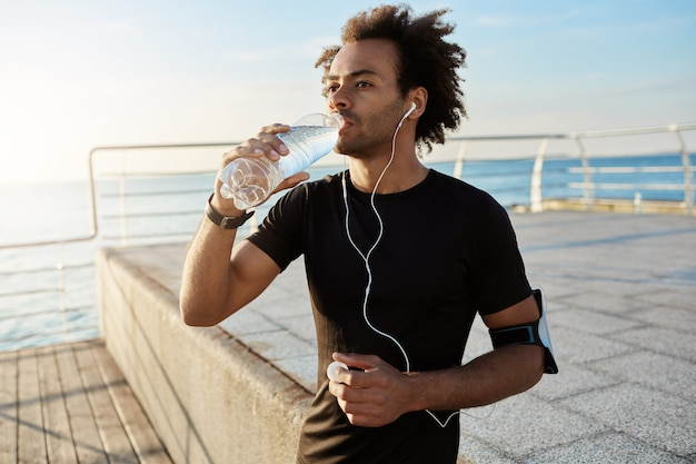 Fit male athlete drinking water out of plastic bottle after jogging on the pear in the morning